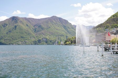 Mountainside villas and appartments at lake with waterfountain in the city of Lugano in Switzerland Stock Photo - 16712625