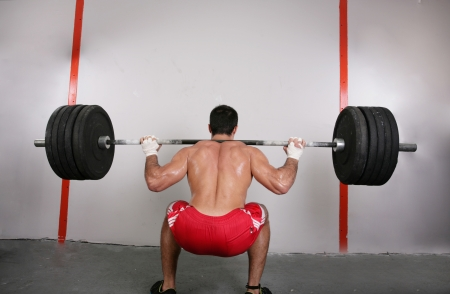 The concept of power and determination of a man lifting a weight bar.  Back squat crossfit exercise.  Focus on the back. photo