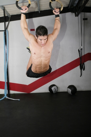 Ring dip crossfit exercise over a dark background. Stock Photo - 16873517