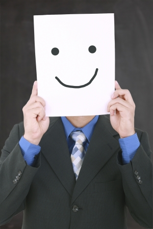 Young businessman hiding his face with a white billboard with a smiley face on it 