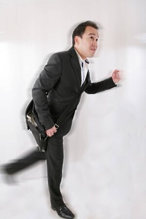 Full length of business man with briefcase running on white background Stock Photo - 17165558