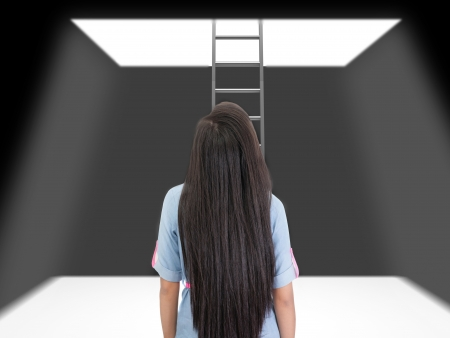 loophole: woman standing in a pit looking up to the ladder that leads out in to the light.