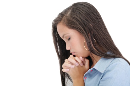 praying together: A young woman praying with her hands together on white background  Stock Photo