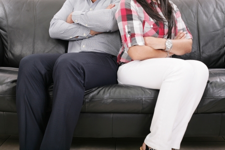 couple arguing: Couple sitting of the couch having problems in their relationship