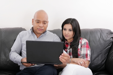 Young couple thinking and looking at a laptop computer photo