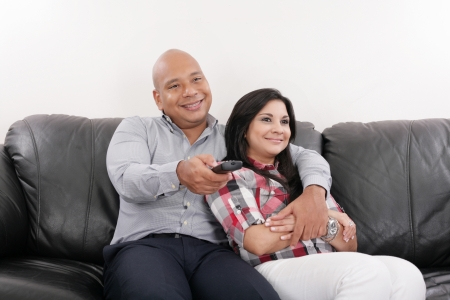 Young couple watching tv on a sofa photo