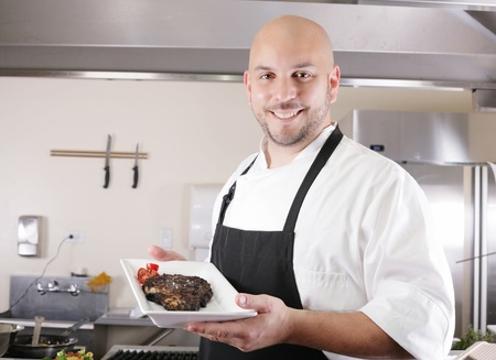 young male chef presenting a juicy ribeye steak with tomatoes photo