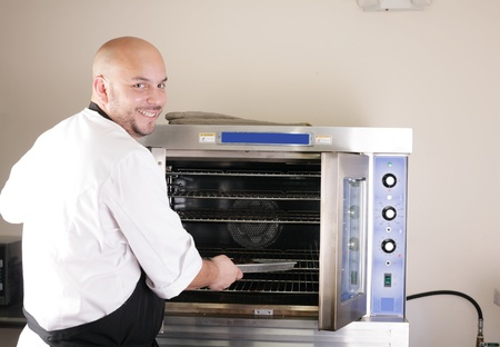 Happy young chef cooking steak in the oven  photo