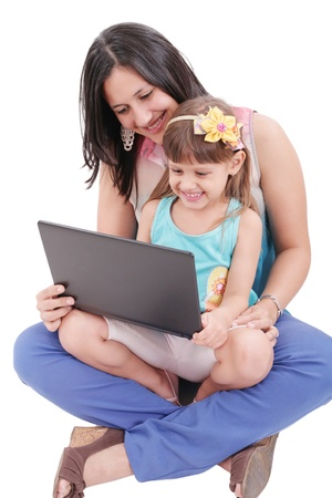 Young mother and daughter looking at laptop.    Focus in the mother. photo