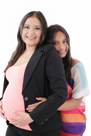 Hispanic Daughter Hugging her businesswoman Pregnant Mother  photo