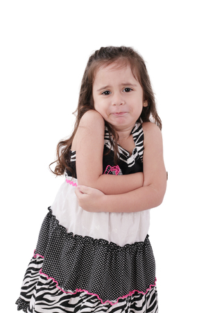 angry little girl in dress with arms crossed on white background photo