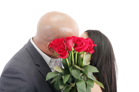 Two young dates kissing behind a bouquet of red roses photo