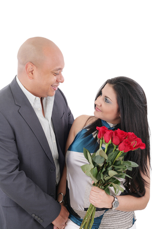 young couple with bouquet of roses looking at each other photo