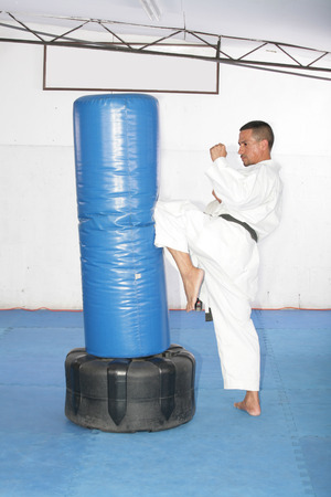 forceful: Athletic black belt karate giving a forceful knee kick during a training with a boxing bag