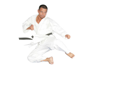 Black belt karate man jumping to give a high kick photo