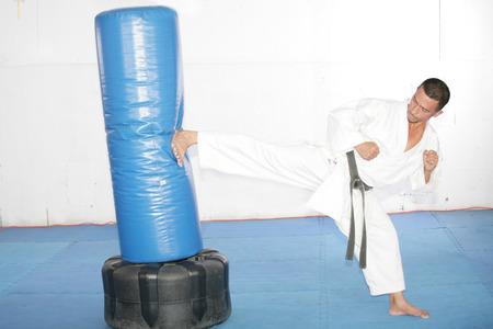 sandbag: Black belt Karate man practicing in a sandbag