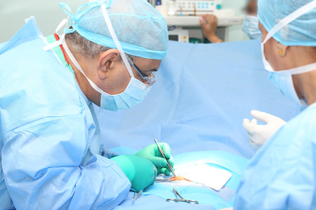 Doctor making a suture in operation room Stock Photo