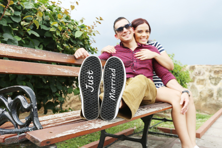 smiing: Young beautiful couple with message Just married in his shoes. Focus in the shoes.