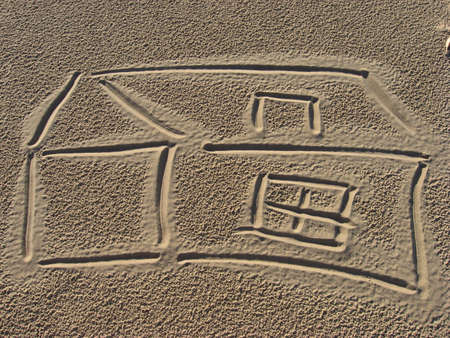 a drowing of home on the sand Stock Photo