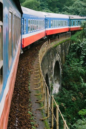 The train rides by rail over a bridge through the jungle in Vietnam. The trip from Hanoi to Ho Chi Minh. Foto de archivo