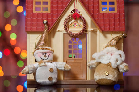 Santa Claus and Snowman against the beautiful house photo