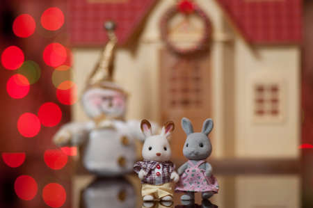 remarkable pair of toy hares against the beautiful house and a snowman photo