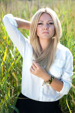 The beautiful young girl in white a blouse does up hair standing in greens Stock Photo