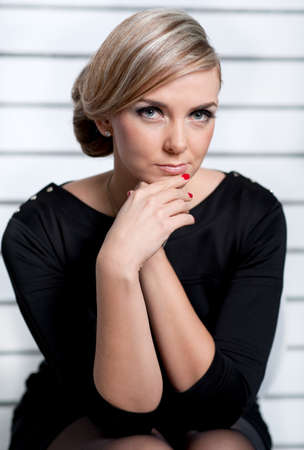 The girl, having crossed hands, sits with a thoughtful look Stock Photo - 17657716