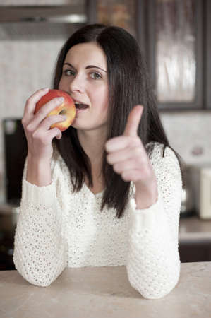 Happy young woman eating an apple in the kitchen photo