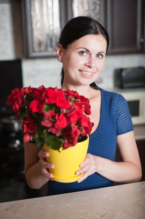 portrait of the young woman with a flower in kitchen