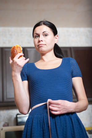 care about the health: young woman holds pie and a measuring tape, care about health Stock Photo