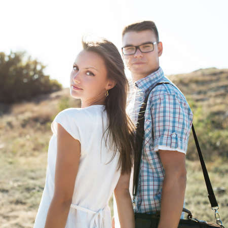 young couple in love walking, holding hands in warm, sunny, summer day. man in a plaid shirt, the woman in a white dress. love. family. happiness. outdoor photo