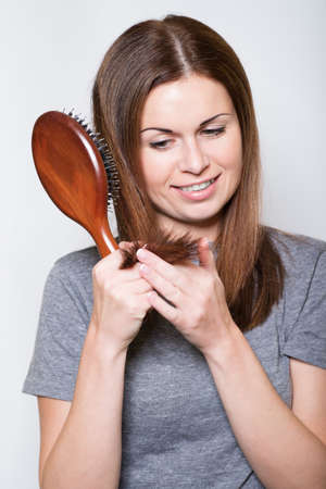 Young brunette beautiful lady combing long hairs on white Stock Photo