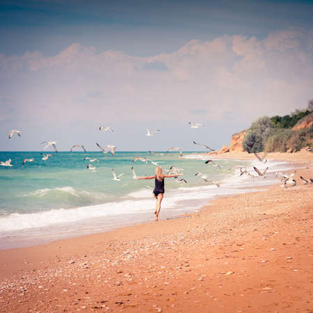 Beautiful young woman running in sea coast on sunny summer day photo