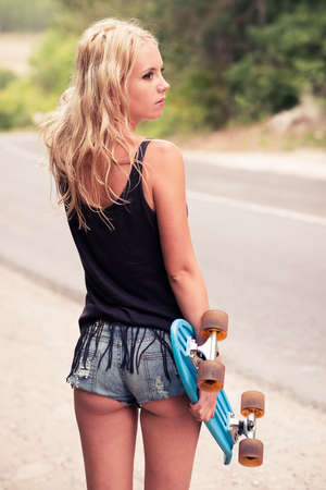 Beautiful young girl hipster with skateboarding in the afternoon. Outdoors, lifestyle photo