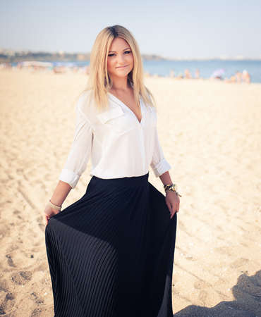 young beautiful woman blonde poses on a beach. dressed in a white shirt and a black skirt. fashion model photo