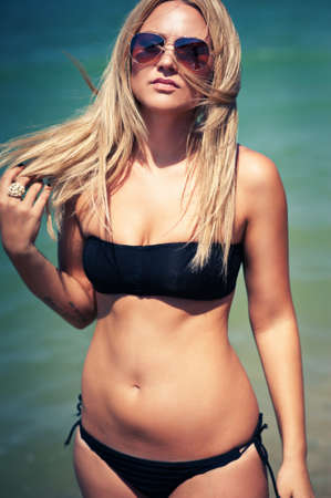 beautiful sexy stylish blond Caucasian young woman model  with perfect sunbathed clean skin  in black swimsuit outdoors in vogue style photo