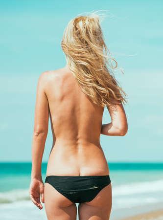 beautiful young woman in sexy bikini at the beach.   photo