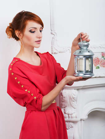 beautiful girl with a lamp shines the room photo