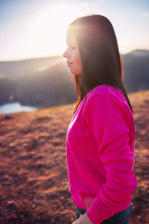 Woman enjoying freedom and life on beautiful and magical sunset. relaxed and happy.  photo