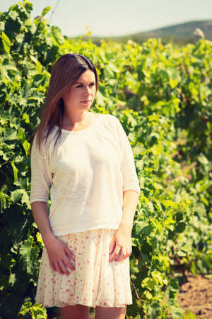 beautiful young woman, walks on a vineyard in a hot summer, sunny day photo