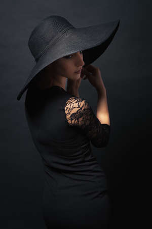 Portrait of a very beautiful girl in black dress and hat