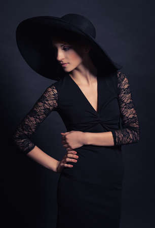 Portrait of a very beautiful girl in black dress and hat. Vogue style photo