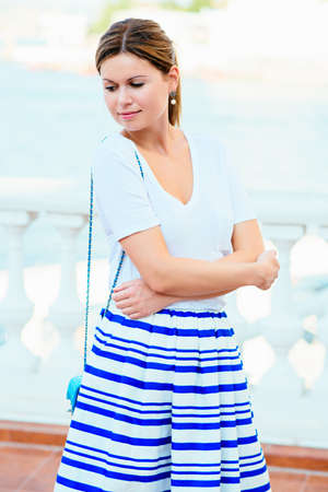 Beautiful blonde young woman wearing fashionable clothes on summer street photo