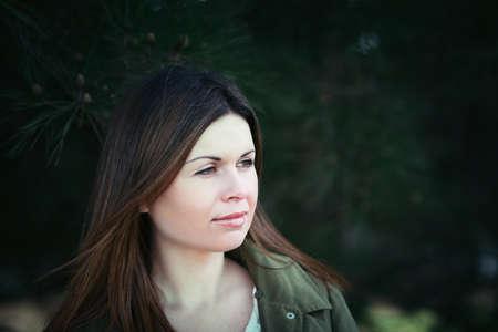 Fashion young woman outdoor portrait. Beautiful girl posing among green trees photo