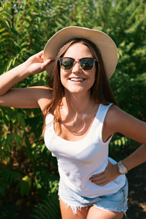 Beautiful young woman in stylish hat and jeans shorts posing. Hipster style. Summer time Stock Photo