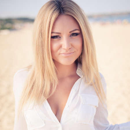 young beautiful woman blonde poses on a beach. dressed in a white shirt and a black skirt. fashion model