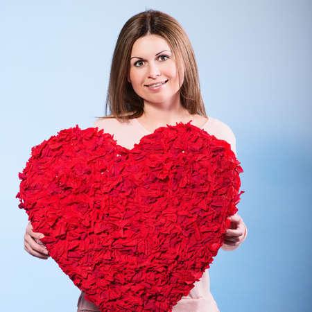 Heart. Love symbol. Portrait of beautiful happy woman hold Valentine day symbol. Isolated studio background female model. Beautiful girl.  photo