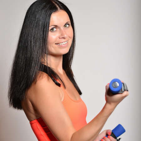 energetic: Happy fitness woman lifting dumbbells smiling cheerful, fresh and energetic.   Stock Photo