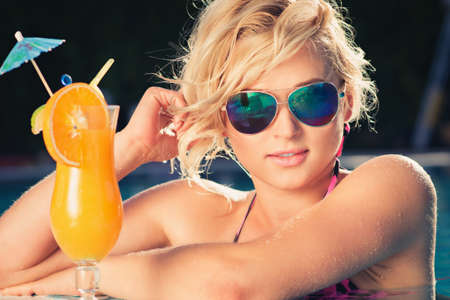 hot drink: beautiful girl in sunglasses with fresh orange juice in luxury pool. Vogue style